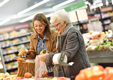 woman helping a senior with grocery shopping